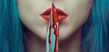Young woman kissing a knife in blood. Halloween or horror theme. Close-up image of red lips