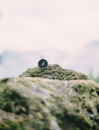 Magnetic compass on stone covered with moss outdoor, concept of travel and hiking.