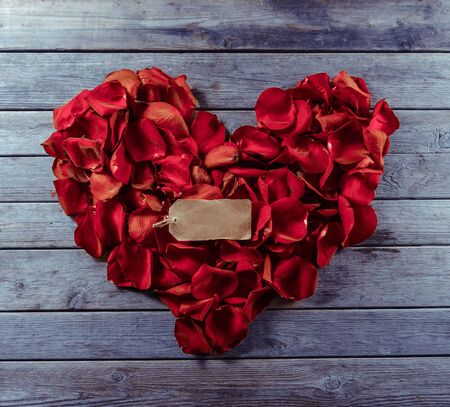 Rose red petals in the shape of heart and blank card, space for text Imagens