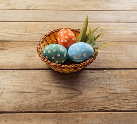 Three Easter colored eggs in a basket on a wooden table, space for text