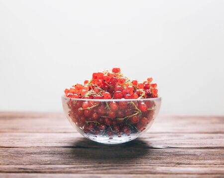 Fresh red currant in a glass bowl on a wooden background, side view. Copy-space in upper part of image.