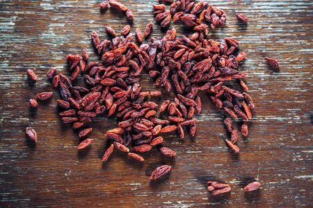 Goji berries are scattered on the wooden table