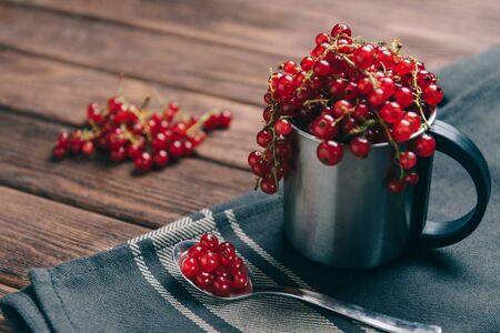 Fresh red ripe currant in a metal cup and on spoon on napkin.