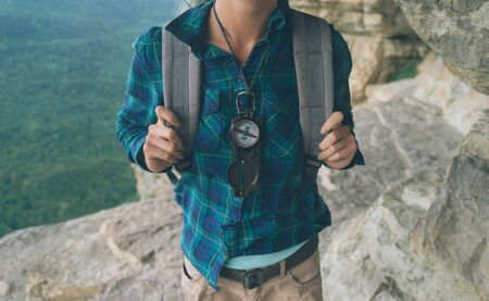 Unrecognizable female traveler standing with compass on cliff in summer