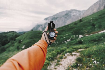 Male explorer searching direction with compass in summer mountains, point of view. Imagens