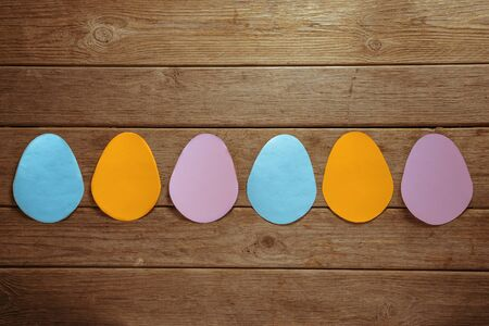 Many colorful Easter paper eggs on a wooden background