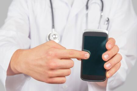 Man doctor is pointing on mobile phone, space for text