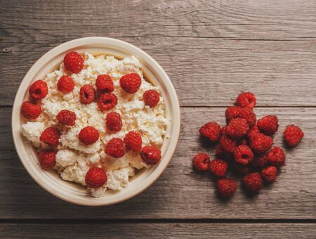 Curd with ripe fresh raspberries in a bowl on wooden background, top view 写真素材
