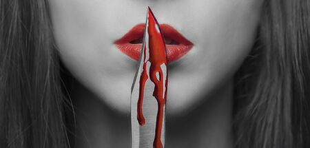 Dangerous young woman kissing a knife in blood. Halloween or horror theme. Black and white image with red elements Stok Fotoğraf - 129892515