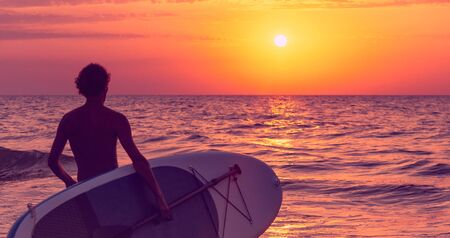 Unrecognizable young man with SUP board going to the sea at sunset.