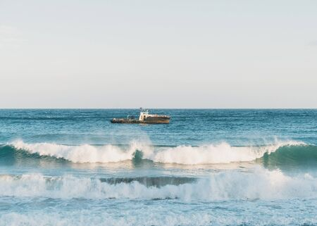 Boat in the sea at windy weather, sea waves with foam Reklamní fotografie