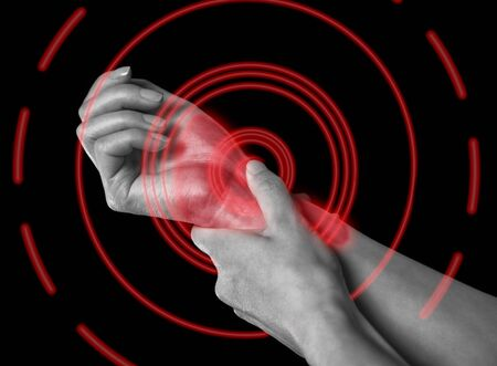 Unrecognizable woman holds her hand, pain in the wrist, monochrome image, pain area of red color