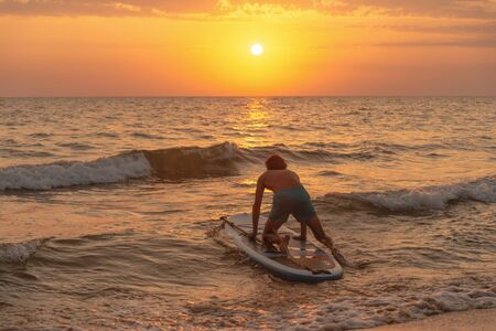 Sporty young man on SUP paddle board going to the sea at sunset.