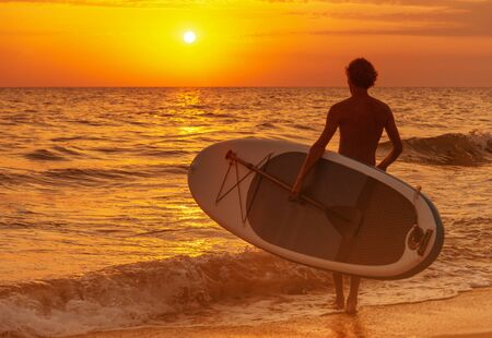 Young man with SUP board going to the sea at sunset, beach vacations.