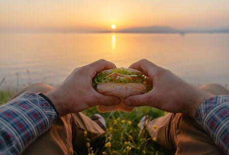Young man holding fresh tasty burger sandwich and relaxing by the sea at summer sunset outdoor, point of view. Stok Fotoğraf