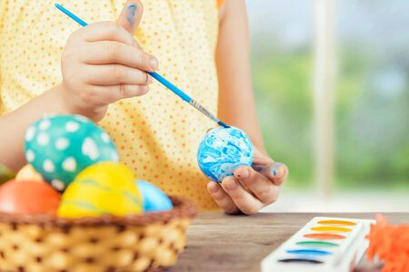 Child is painting egg in blue color for Easter holiday, face is not visible