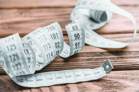 Measuring tape for tailoring on a wooden table, close-up. Stok Fotoğraf