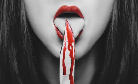 Dangerous young woman licking a knife in blood. Halloween or horror theme. Black and white image with red elements Stok Fotoğraf