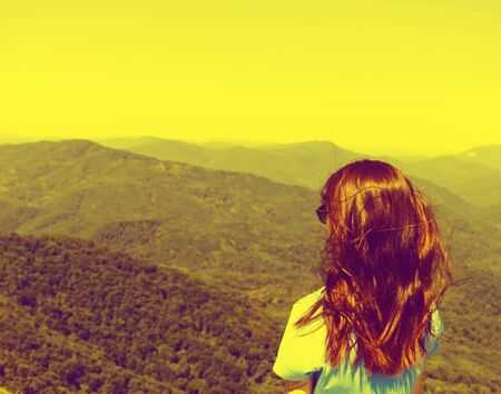 Traveler young woman looking at mountains outdoor. Image with retro vintage color effect. Stok Fotoğraf