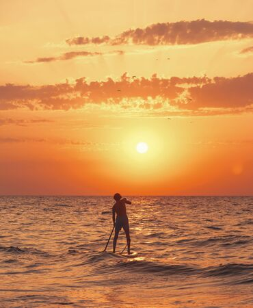 Young man paddling on a SUP board in the sea at sunset, rear view.