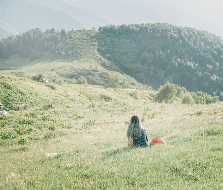 Young woman is resting on summer mountain meadow in sunny day, rear view.
