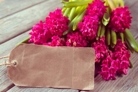 Red flowers hyacinths and a blank card on a wooden table, space for text Stok Fotoğraf