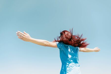 Happy young woman with fluttering long hair standing with raised arms on background of blue sky. Reklamní fotografie