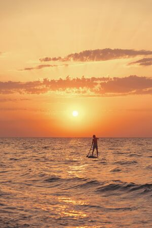 Silhouette of young man floating on stand up paddle board, SUP, in the sea at sunset.