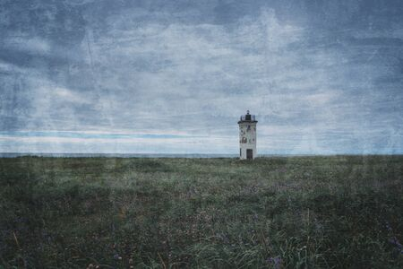 Old dark mysterious lighthouse on summer meadow. Image with textured effect