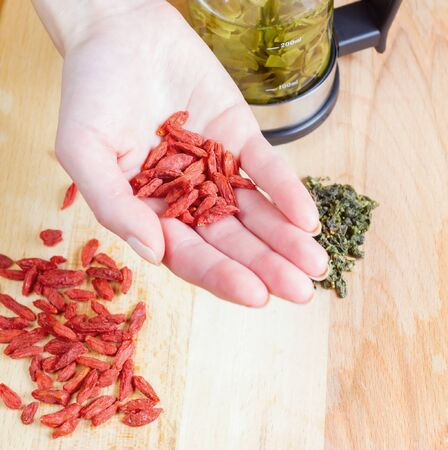 Woman hold goji closeup. Teapot, green tea, goji on the table closed up