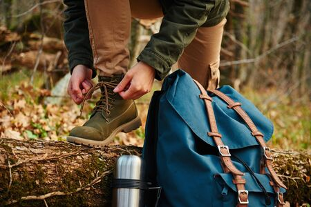 Female hiker tying shoelaces outdoors in autumn forest, near flask and backpack. View of legs. Hiking and leisure theme