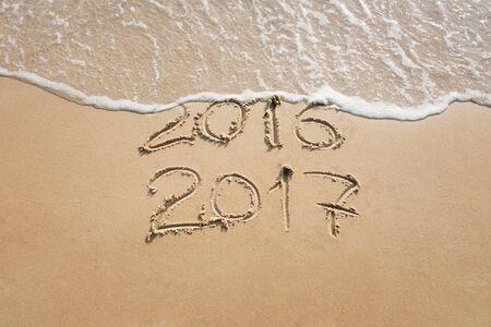 Stary rok 2016 i nowy rok 2017 wypisane na piasku nad morzem, fala zmywa 2016