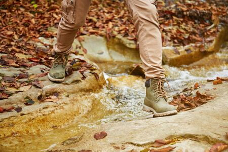 Hiker woman crossing a river in autumn forest, view of legs. Hiking and leisure theme