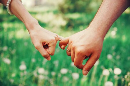 Married young loving couple holding hands each other in summer park, view of hands