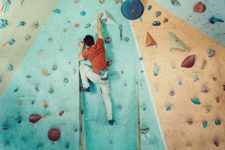Freier Kletterer junger Mann, der künstlichen Felsbrocken drinnen klettert