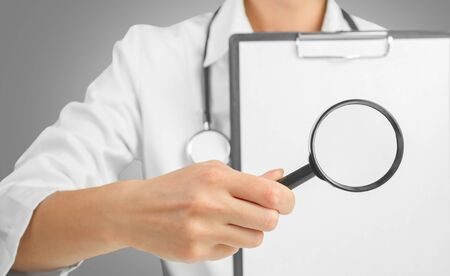 Doctor showing clipboard with a magnifying glass. Space for text