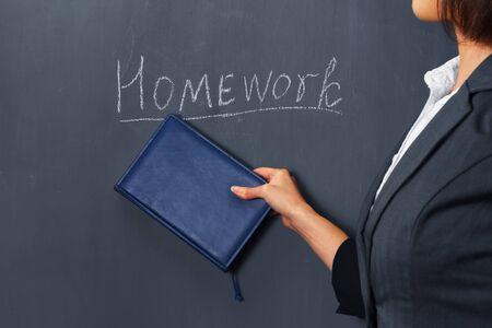 Unrecognizable female teacher indicates by book on homework Banco de Imagens