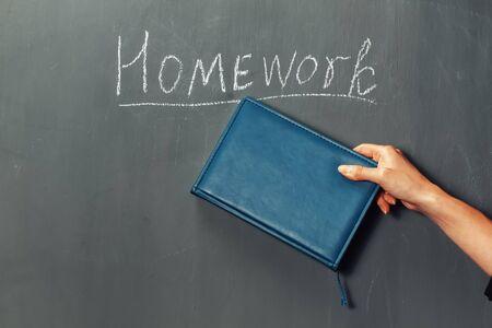 Human hand indicates on word homework on a blackboard