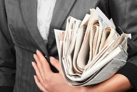 A woman in a jacket holds a stack of newspapers