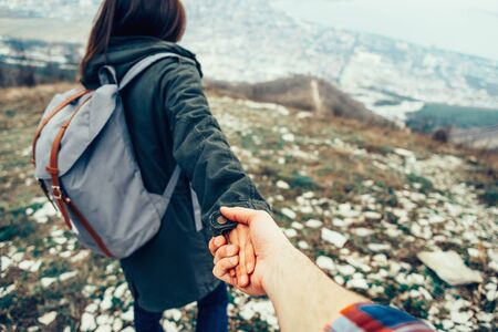 Hiker young woman holding man's hand and leading him on nature outdoor. Couple in love. Focus on hands.