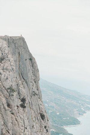 Hombre viajero de pie en el borde del acantilado Foros kant sobre la costa, Crimea, Rusia. Concepto de persona mínima en paisaje masivo.