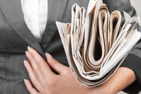 A woman holds stack of newspapers