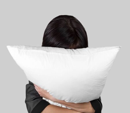 Tired female office worker rests with pillow, concept of stress work