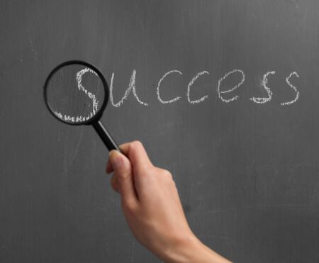 Human hand with a magnifying glass indicates on the word success Banco de Imagens