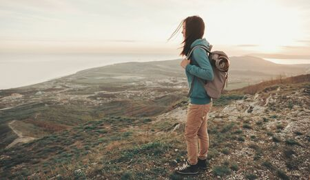 Beautiful traveler young woman with backpack walking in mountains. Toned image Stock Photo