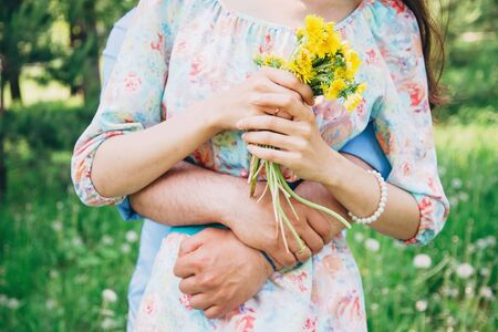 Married loving couple resting in summer, man embraces a woman in summer park. Woman holding bouquet of yellow dandelions