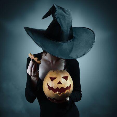 Mujer en traje de bruja abre calabaza de Halloween tallada