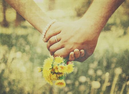 Young loving couple holding hands each other with bouquet of yellow dandelions in summer park, view of hands. Vintage image