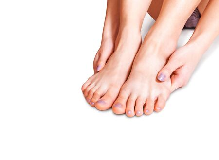 Tanned female feet on the white background