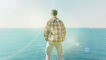 Young man enjoying view of sea in summer, rear view. Image with sunlight effect